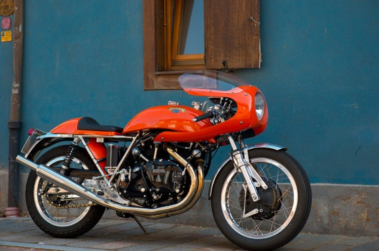 "Godet 1330 Cafe Racer in a stunning racing orange. There is a story beside this picture says Pierre. ""We were riding along on our Nortons in the French Vosges Mountains, and we saw a bunch of Vincent Motorcycles coming at us on the other side of the road. We stopped them and recognized our friend Serge Raspoutine Vollard with Fritz Egli and Patrick Godet on a rally with the club. They were lost and we shown them the right way, then we went together for a beer in a local pub, that's where Vincent took this picture."" 