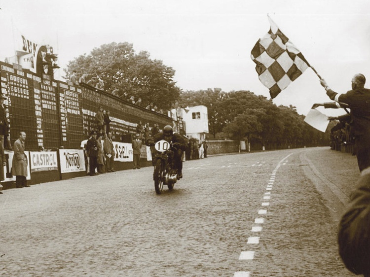Alex Phillip hitting the finish line as the winner at an average speed of 78.58mph with his stock 1947 Rapide for this second edition of the Clubman TT. | Picture courtesy of Mortons Archives
