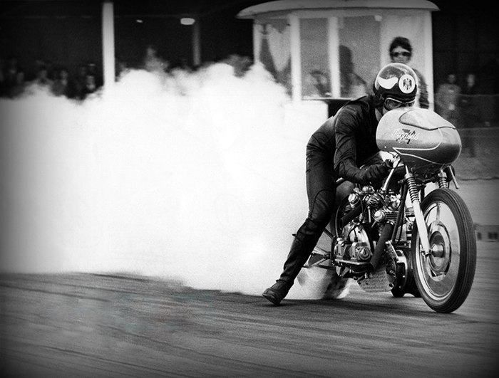 """A great shot of Derek burning the rear slick; this shows the ""short"" exhaust pipes experimented with for a few meetings. Although they produced a lot of low-end torque, ultimately they didn't improve the elapsed time. 1971 Santa Pod Raceway, UK"".  Picture and information © TeamPegasus"