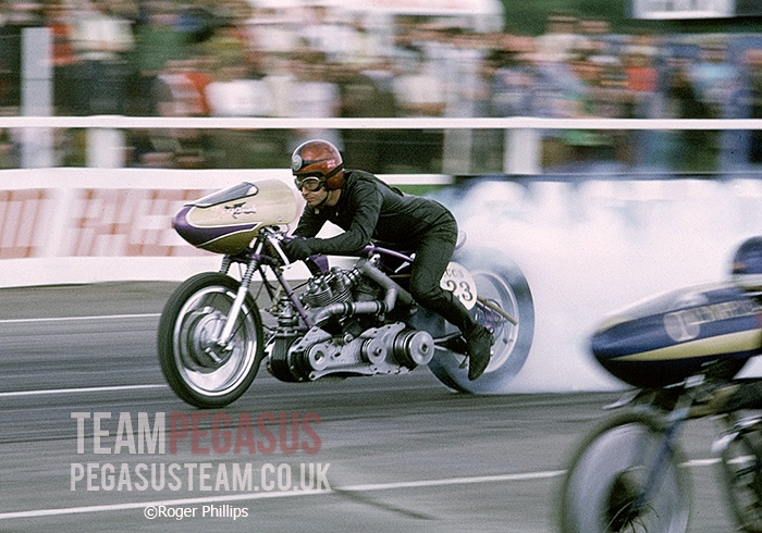 """Another great action shot from Roger Phillips showing Mick Butler on the Pegasus-Vincent employing his neat ""economical"" riding style with the nosecone of arch rival John Hobbs just coming into shot. 1971 Santa Pod Raceway, UK"". Information TeamPegasus and picture © Roger Phillips"