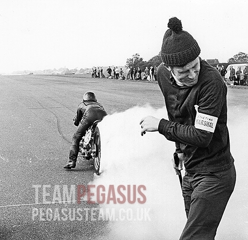"""A great shot from an unknown photographer taken at an NSA sprint event with Ian proving the job of a startline marshal can be a hazardous one. In the ""Blog"" pages you will find a short cine clip of this run. 1969, RAF Debden, Essex UK"". Picture and information © TeamPegasus"